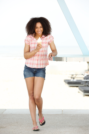 Full length portrait of a beautiful young woman in summer shorts standing outdoors with ice cream photo