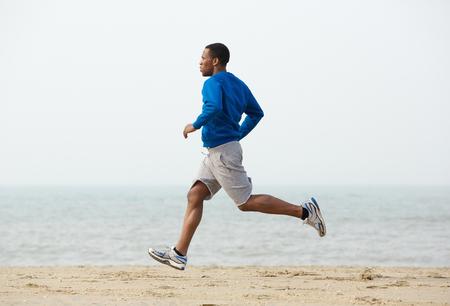 and the horizontal man: Healthy young black man jogging at the beach