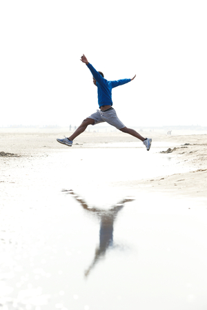 Young man running and jumping at the beach. Athletic male in sportswear outdoors  photo