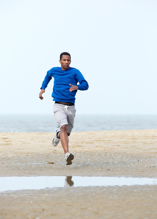 Active young man jogging at the beach. Running exercise photo