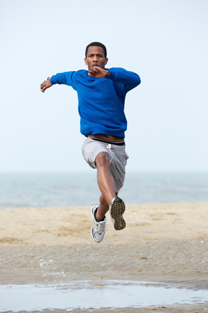 Young male athlete running and jumping at the beach. Young man exercising outdoors photo