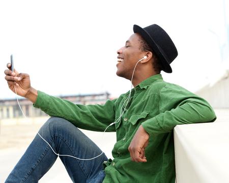 listening to music: Retrato de un hombre joven y sonriente escuchar m�sica en el tel�fono m�vil Foto de archivo