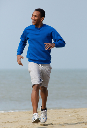 african american man: Handsome young man jogging outdoors at the beach