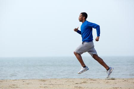 hombres negros: Hombre atlético joven sana que se ejecuta en la playa