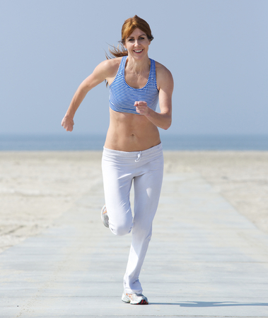 Full length portrait of a healthy middle aged woman enjoying a jog at the beach photo