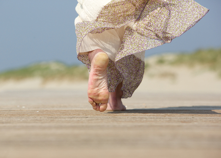 young girl barefoot: Close up rear view of female feet walking away at the beach Stock Photo