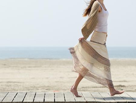 드레스에 맨발로 해변에서 산책하는 한 여성