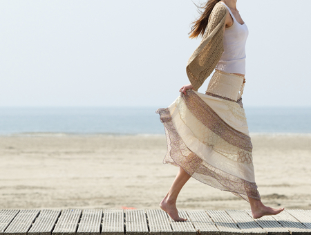 One female walking at the beach barefoot with dress