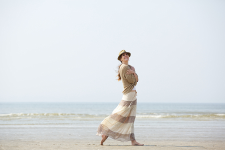 middle aged woman smiling: Portrait of a beautiful middle aged woman smiling and walking on the beach