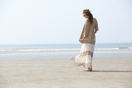 Rear view portrait of a beautiful woman walking on the beach