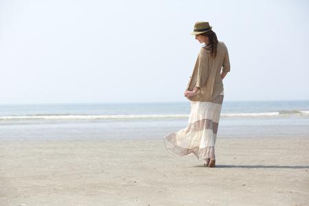 mujer cuerpo completo: Vista trasera retrato de una hermosa mujer caminando en la playa