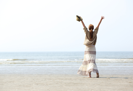 arm raised: Woman with raised arms at the beach celebration from behind