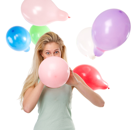 Close up portrait of a beautiful young woman blowing up balloons for a party photo