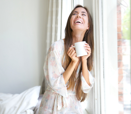 Portrait of an beautiful young woman smiling by window drinking coffee Stock Photo