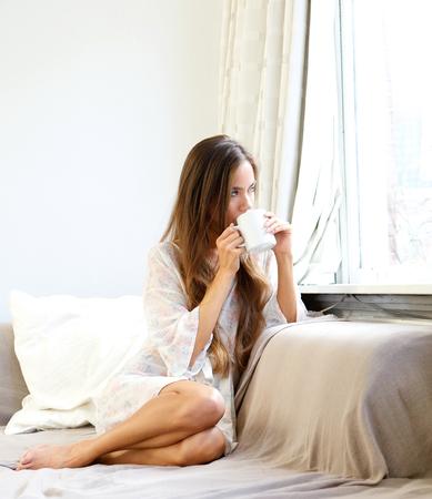 felicidade: Feche acima do retrato de um café bebendo da mulher jovem e bela de manhã e olhar pela janela Imagens