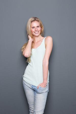 vrouw blond: Portret van een schattige jonge blonde vrouw lachend op een grijze achtergrond