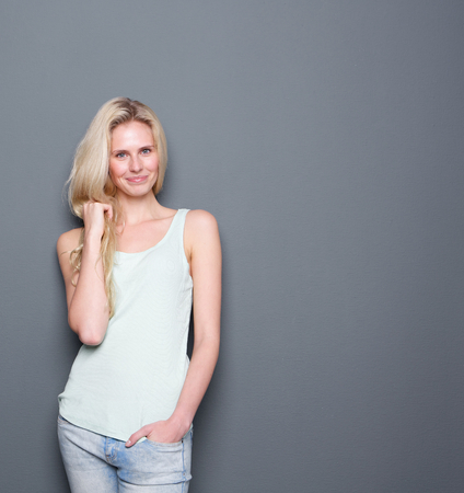 Portrait of a cute young blond lady smiling with hand in hair on gray background Imagens