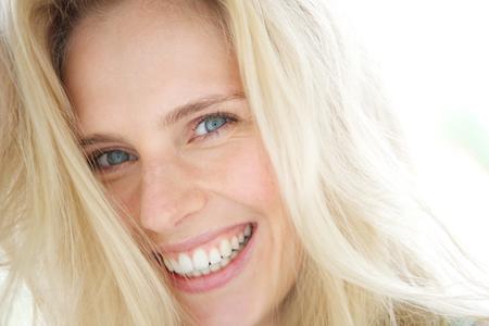 Close-up portret van een vrolijke jonge blonde vrouw lachend