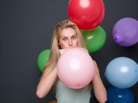 Portrait of a blond woman inflating balloons for a party photo