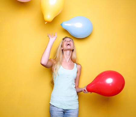 Portrait of a happy young woman laughing with balloons  photo