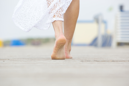 Close up low angle barefoot woman walking away