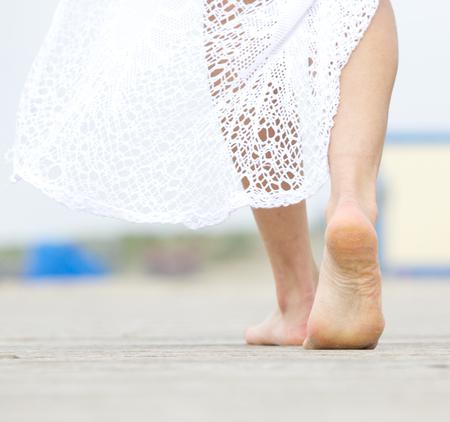 離れて歩いて裸足の女性の肖像画を閉じる