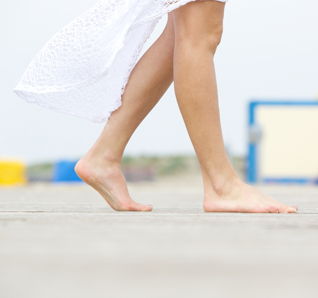 Close up side view of a young woman walking barefoot outdoors