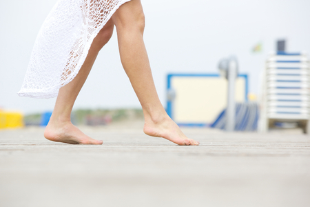 Close up low angle side view of a young woman walking barefoot outdoors