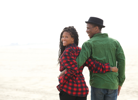 Close up portrait of a happy black couple walking not he beach photo