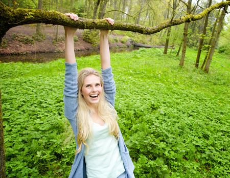 Portrait of a beautiful young woman smiling and hanging on a branch from a tree in the woods photo
