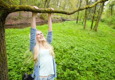 Portrait of a cheerful young woman playing outdoors in the forest photo