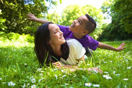 madre soltera: Retrato de una madre joven alegre que juega con su hijo al aire libre