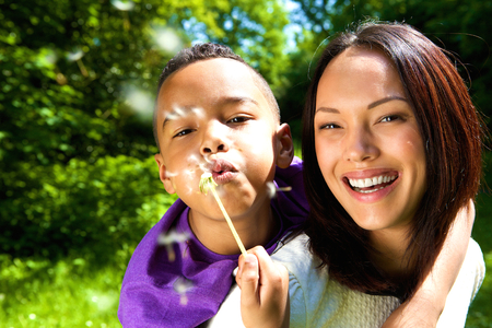 Close up portrait of a smiling mother with son blowing dandelion outdoors