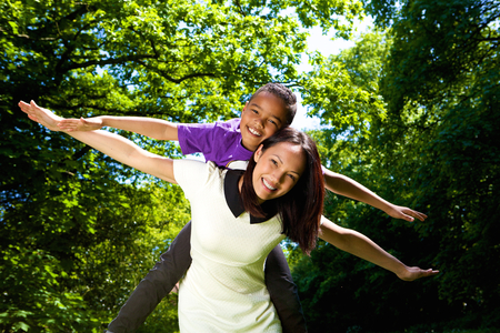 Portrait of a cheerful young mother and son with arms spread photo