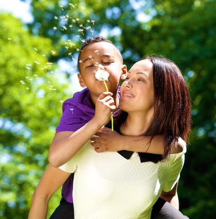 madre soltera: Cerrar un retrato de una madre soltera feliz con el hijo de le�n que sopla Foto de archivo