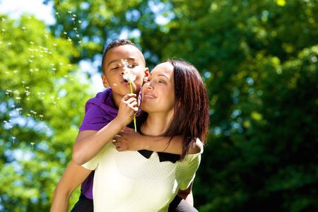 mama e hijo: Close up retrato de una joven madre feliz con el hijo que lleva a cuestas y soplando el diente de le�n