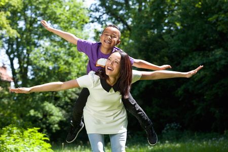 Close up portrait of a joyful mother and son with arms spread pretending to fly