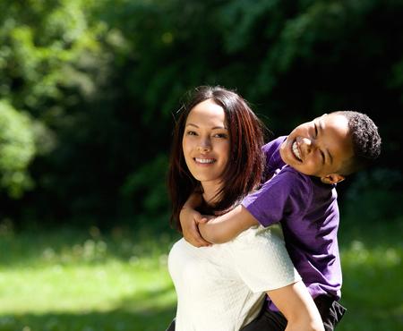 Portret van een alleenstaande moeder met zoon genieten van piggyback rit buitenshuis