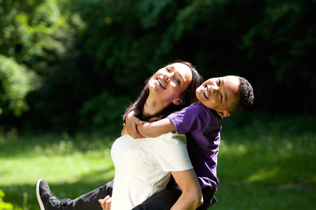single parent: Portrait of a happy mother with son enjoying piggyback ride outdoors Stock Photo