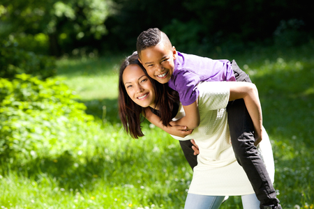 enjoying life: Portrait of a young mother smiling outdoors with happy son