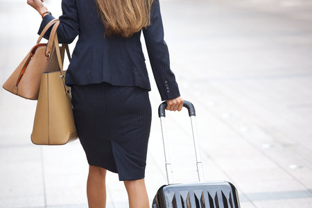 Businesswoman traveling with luggage and handbags in the city Stok Fotoğraf