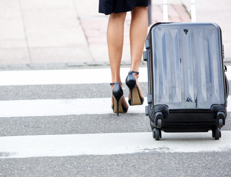 heals: Low section businesswoman crossing street with rolling luggage