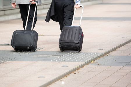a two wheeled vehicle: Two businessmen walking with wheeled luggage on city sidewalk Stock Photo