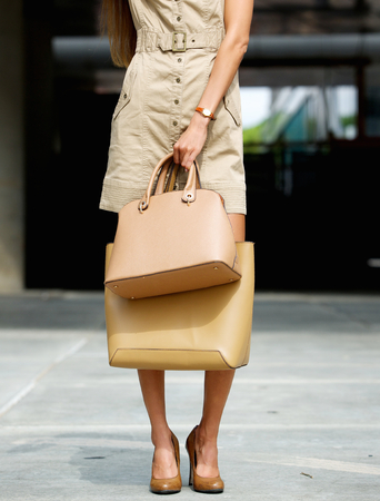 heals: Trendy young woman holding  leather handbags outdoors