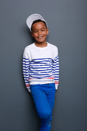 beautiful boys: Portrait of a smiling little boy standing against gray background