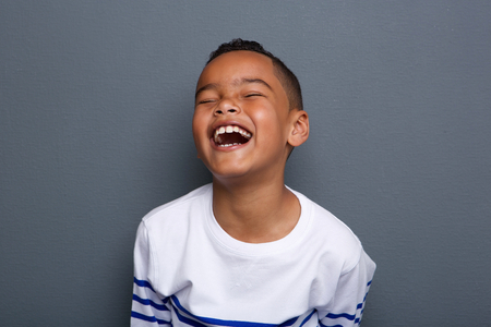 close up: Close up portrait of an excited little boy laughing on gray background