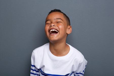 Close-up portret van een opgewonden kleine jongen lachend op een grijze achtergrond Stockfoto