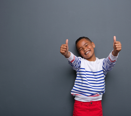 look up: Portrait of a little boy laughing with thumbs up sign on gray background