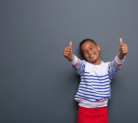 Portret van een kleine jongen lachend met duim omhoog te ondertekenen op een grijze achtergrond