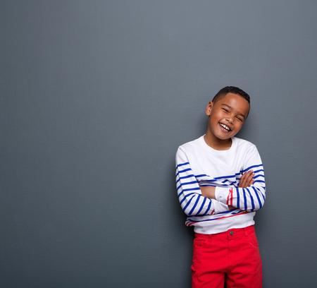 Portret van een schattige kleine jongen lachend met de armen gekruist op een grijze achtergrond Stockfoto